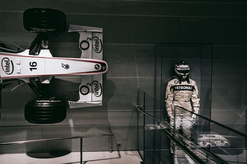 F1 Driver Statue Beside F1 Car