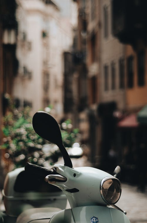 Close-up Photo of a Parked White Motor Scooter