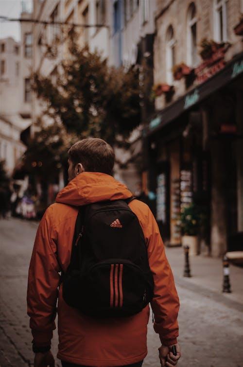 Man in Orange Jacket With Black Adidas Backpack Walks in Middle of Road
