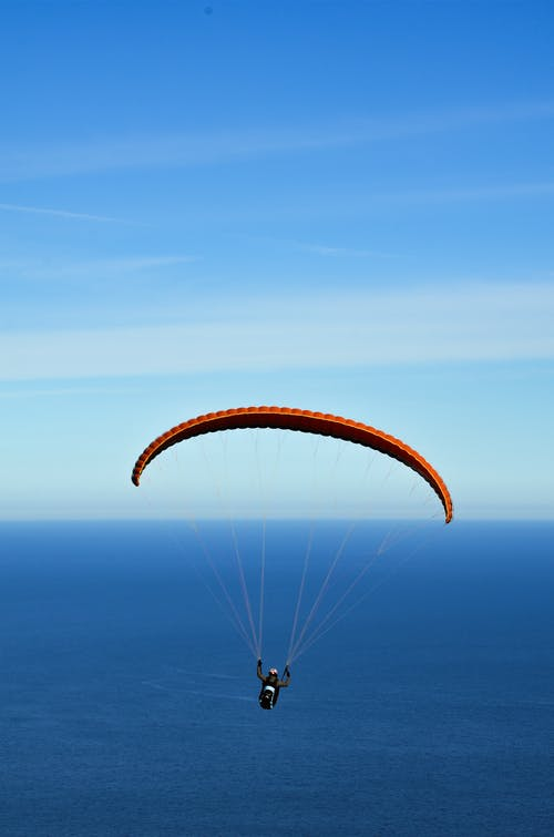 Man on Parachute over Blue Sea