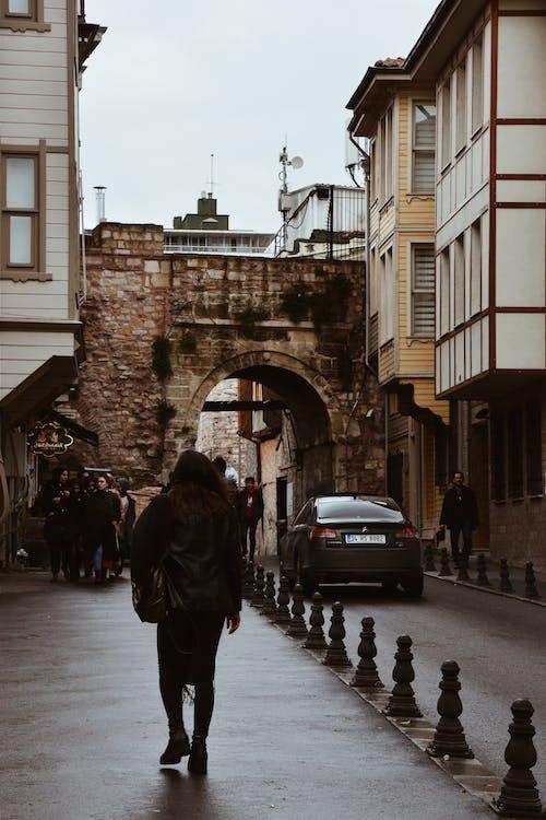Woman Walking on Brown Pavement