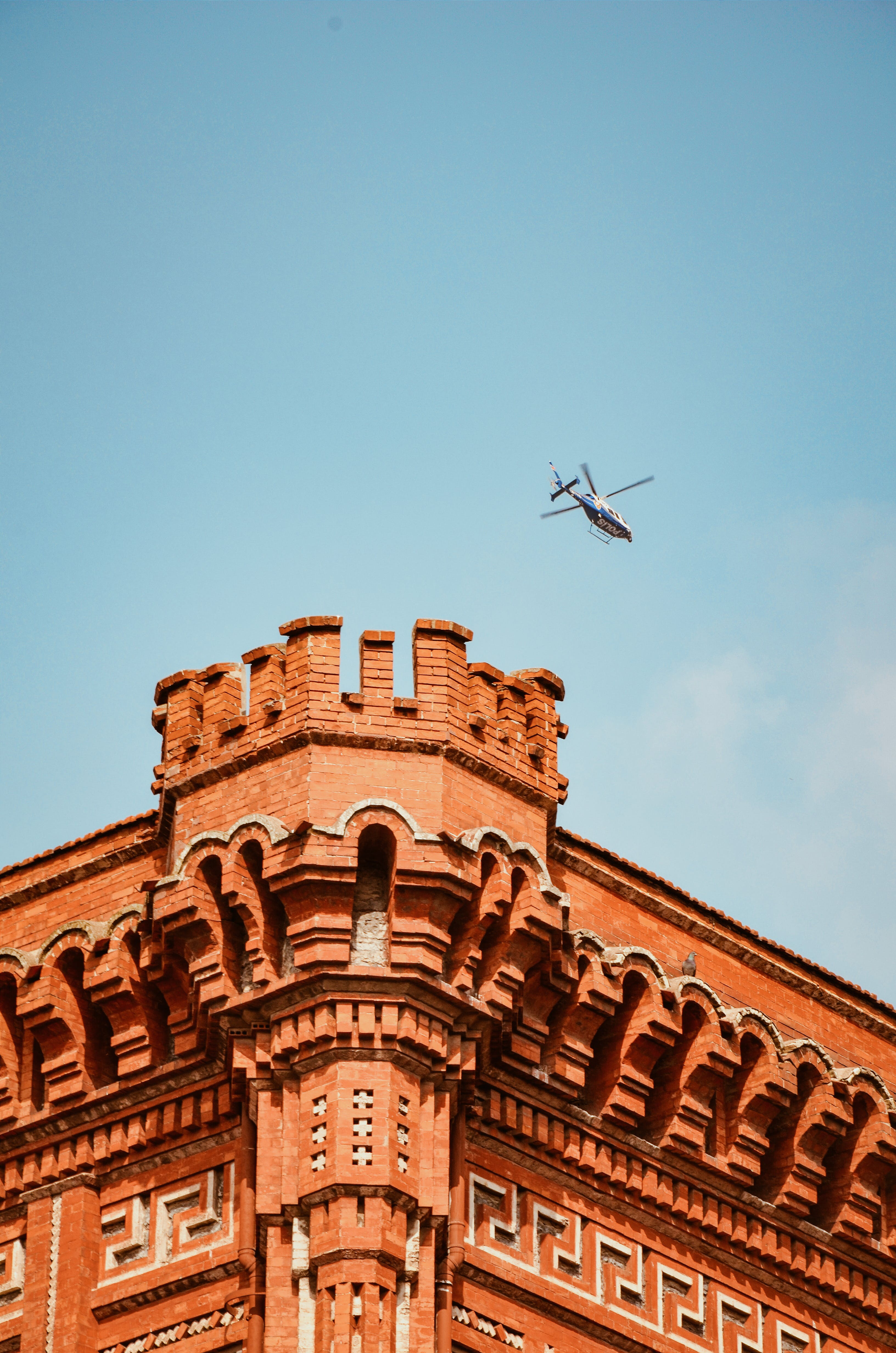 Helicopter Flying Over Brown Building With Turret
