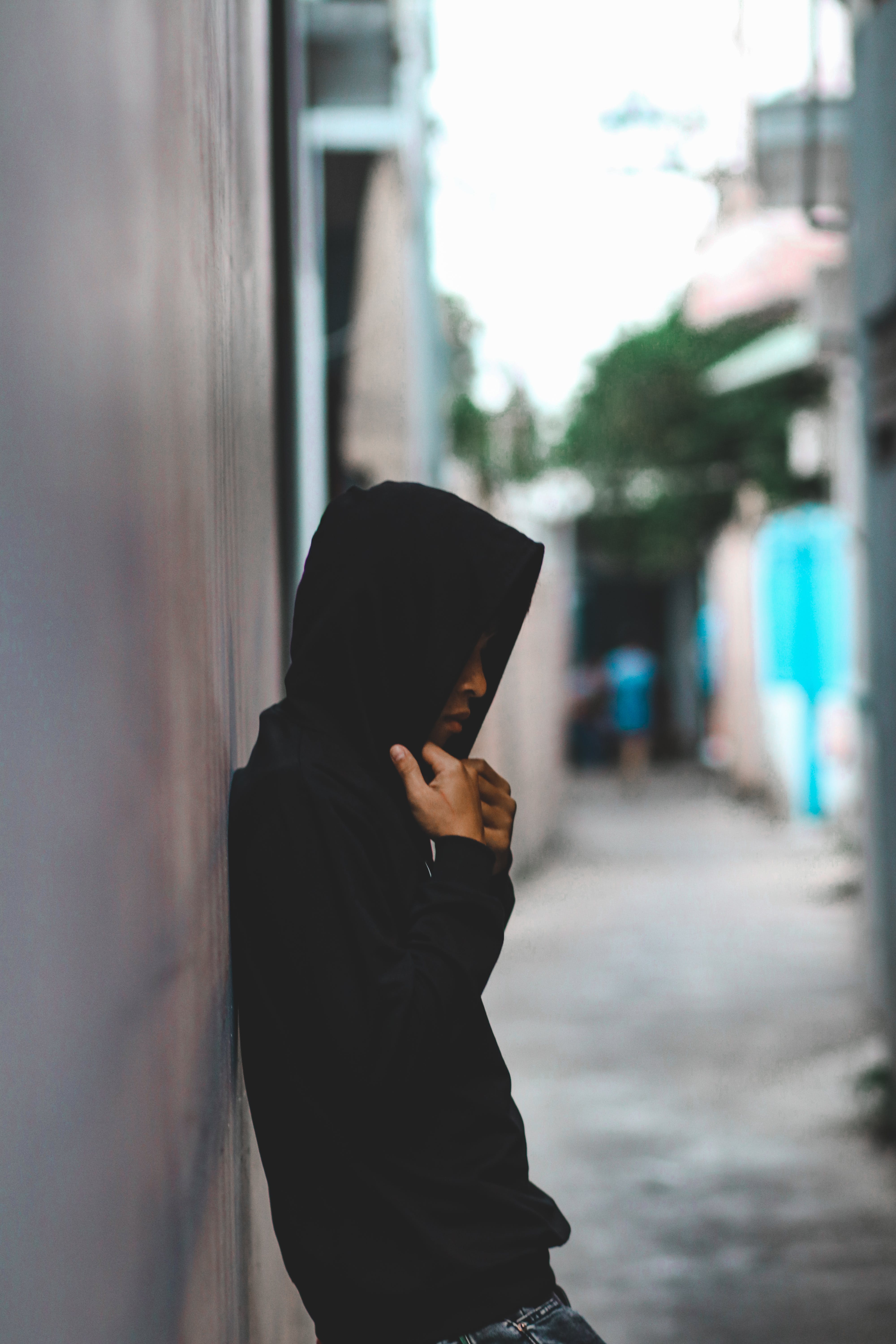Person Leaning On Wall Wearing Black Hooded Jacket