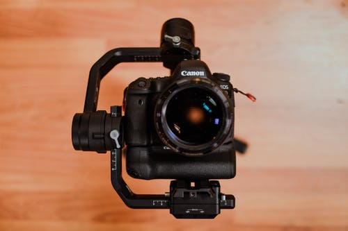 Black Canon Dslr Camera on Brown Wooden Surface