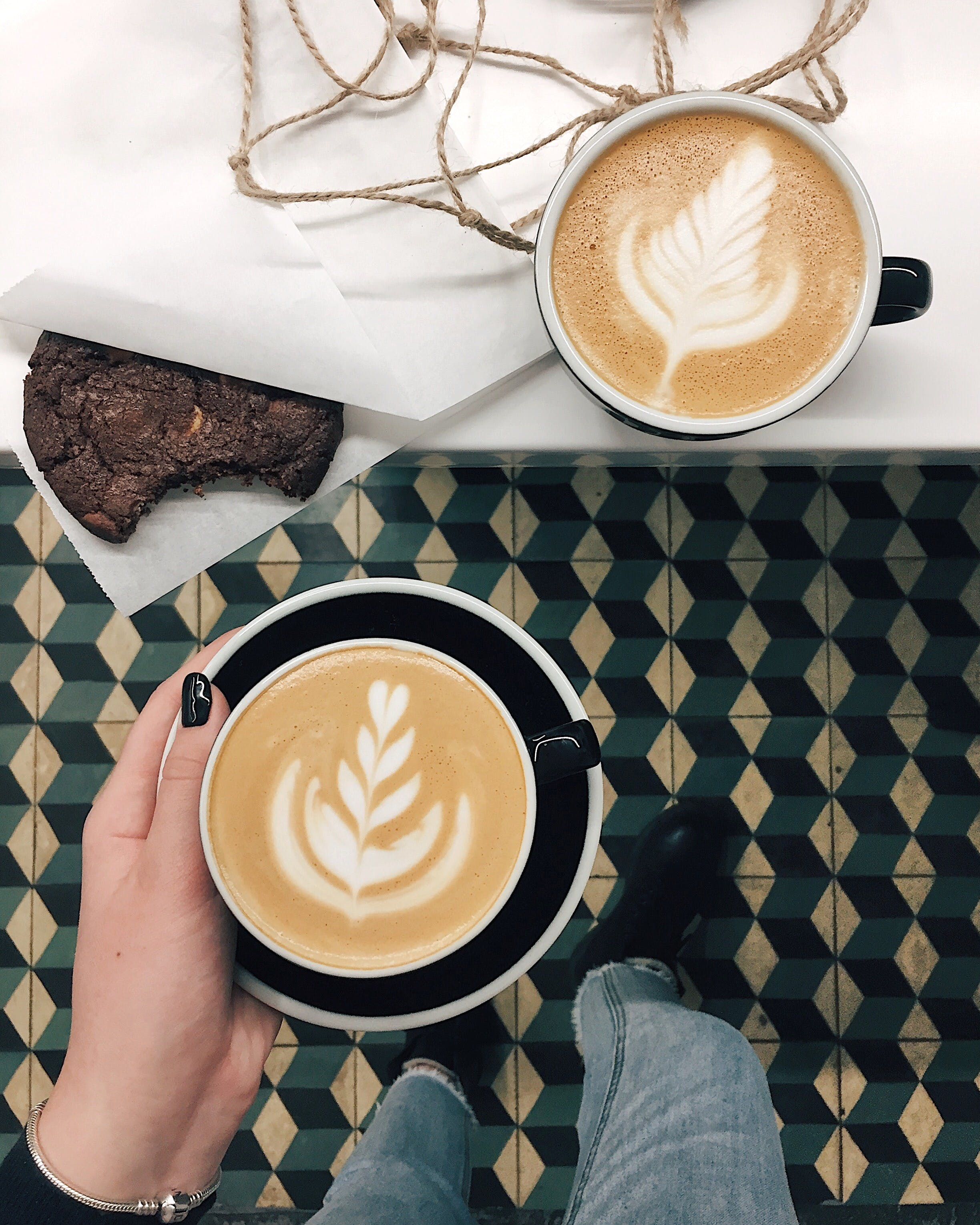 Two Cups of Cappuccinos With Chocolate Cookie on Table