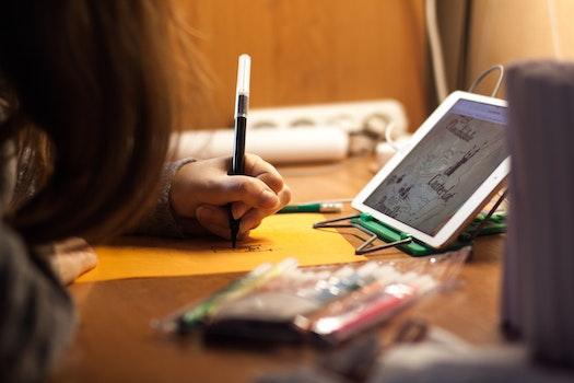 Woman Writing on Orange Paper