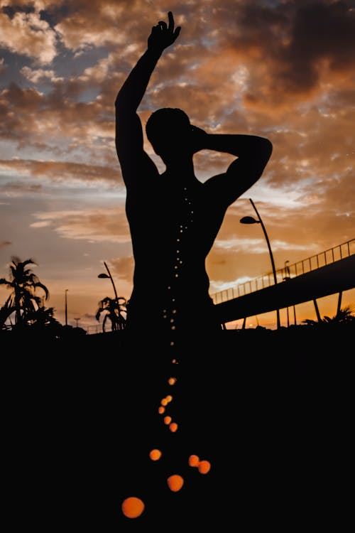 Silhouette Of Man Raising Hand