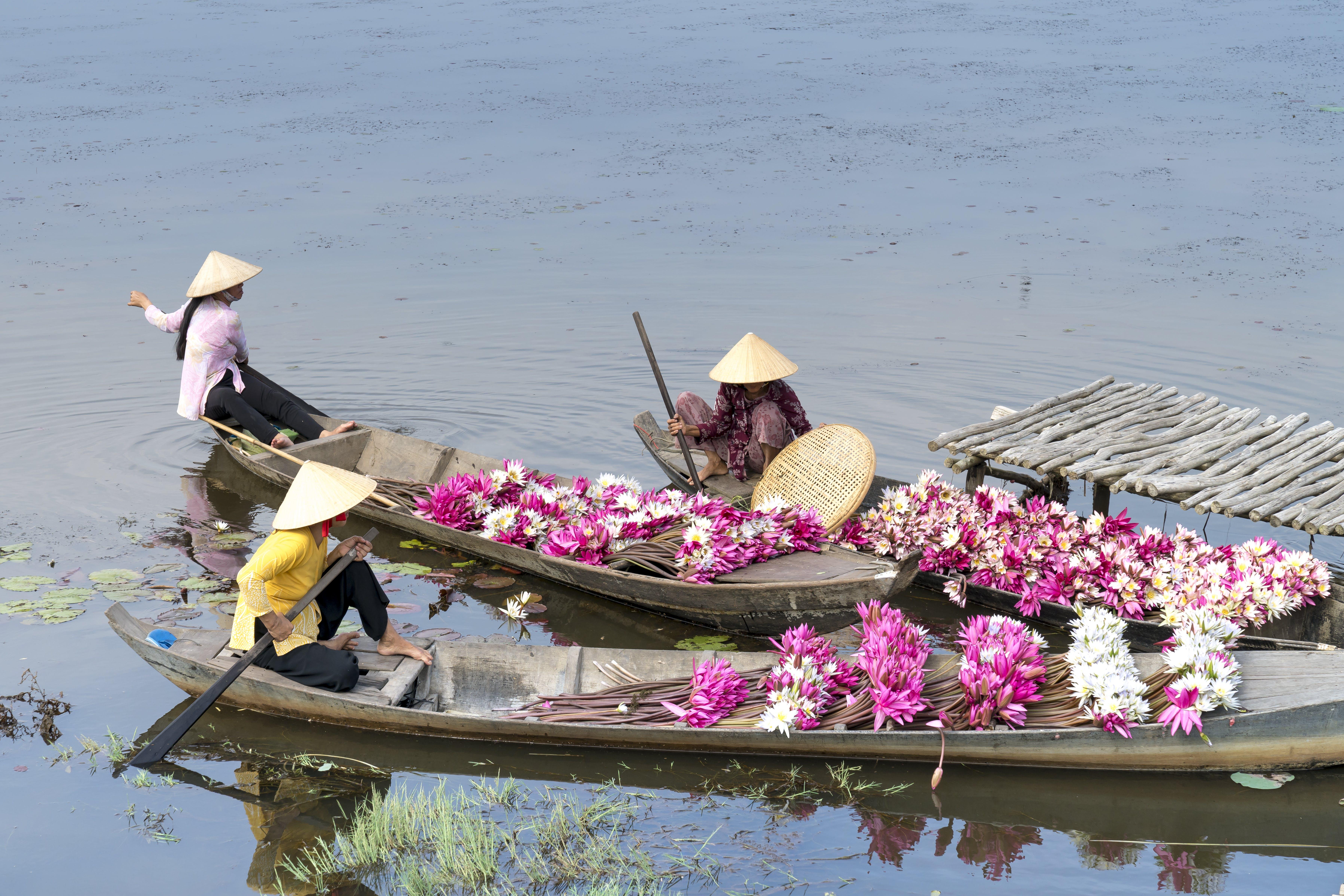 Three Women Sitting On Boats
