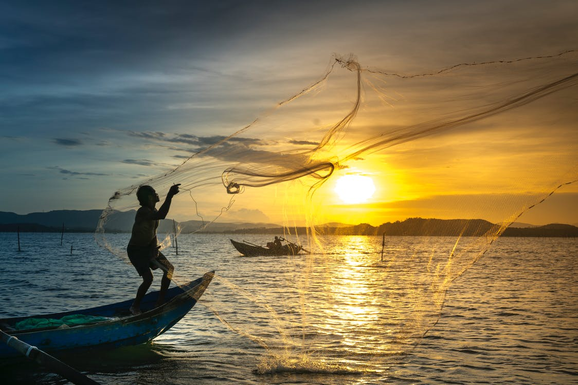 Man Standing On Boat Throwing Net