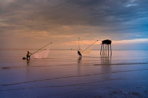 People Fishing Using Net On Ocean