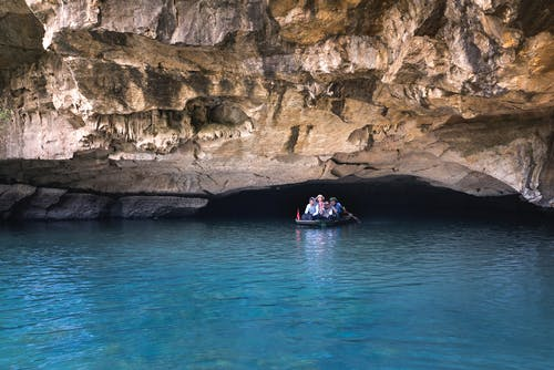 People on Boat Under Cave