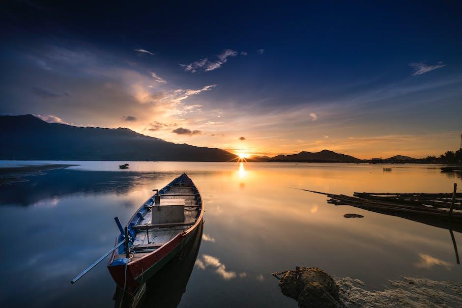 Empty gray canoe boat near shore during golden hour