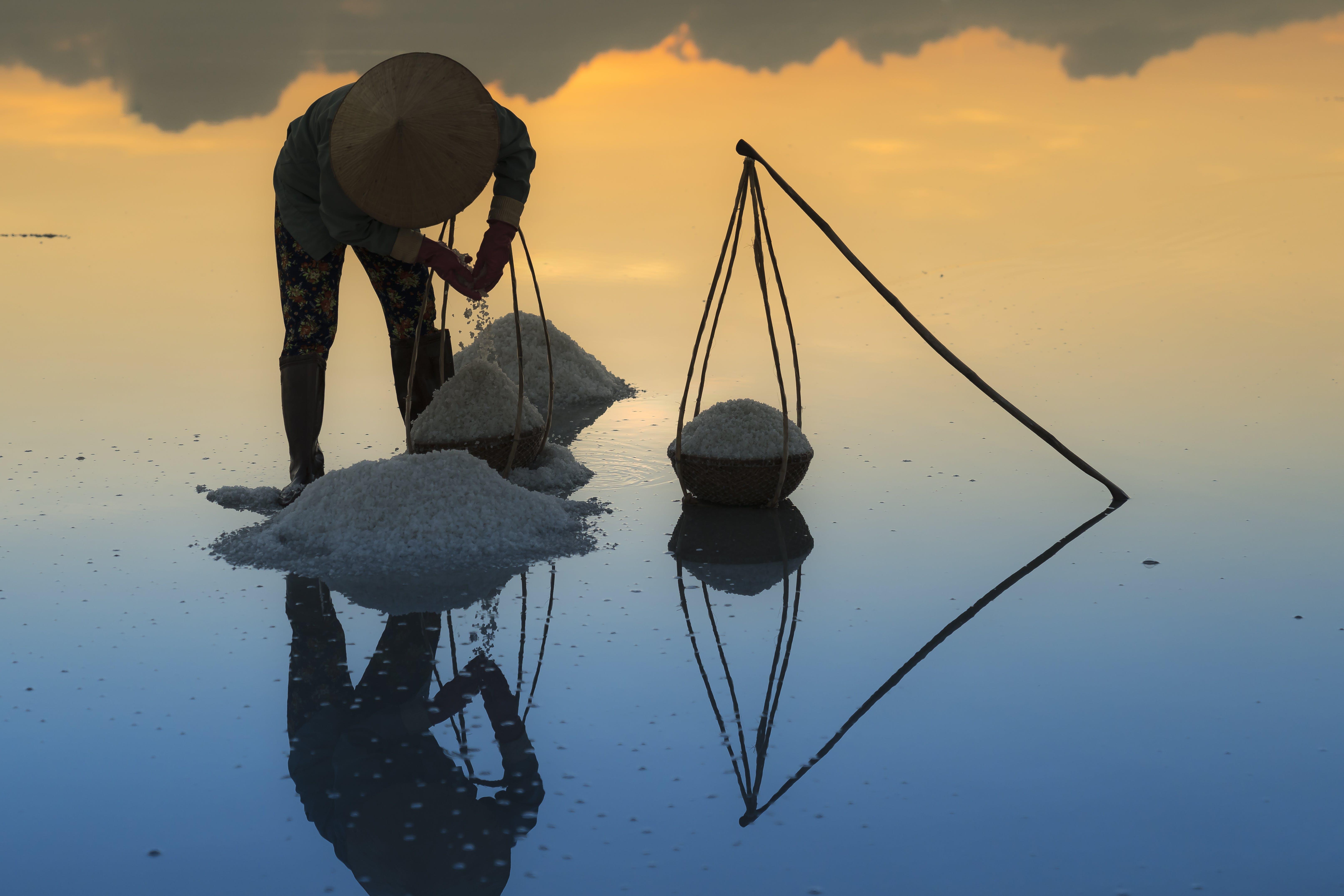 Man Carrying Salt On Basket During Golden Hour