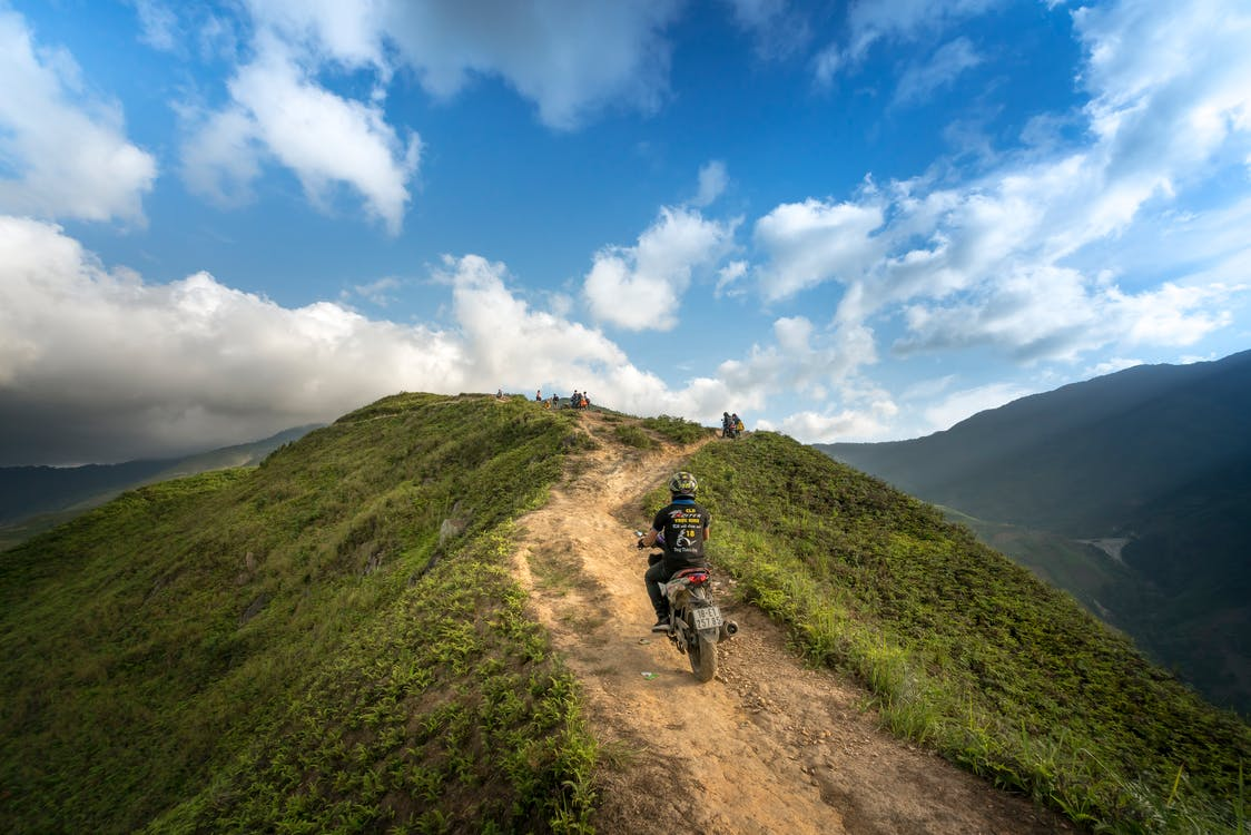Person Riding on Motorcycle on Mountain