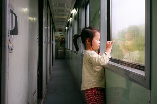 Photo of Girl Standing by Window in Train Hallway Looking Outside While Taking a Photo
