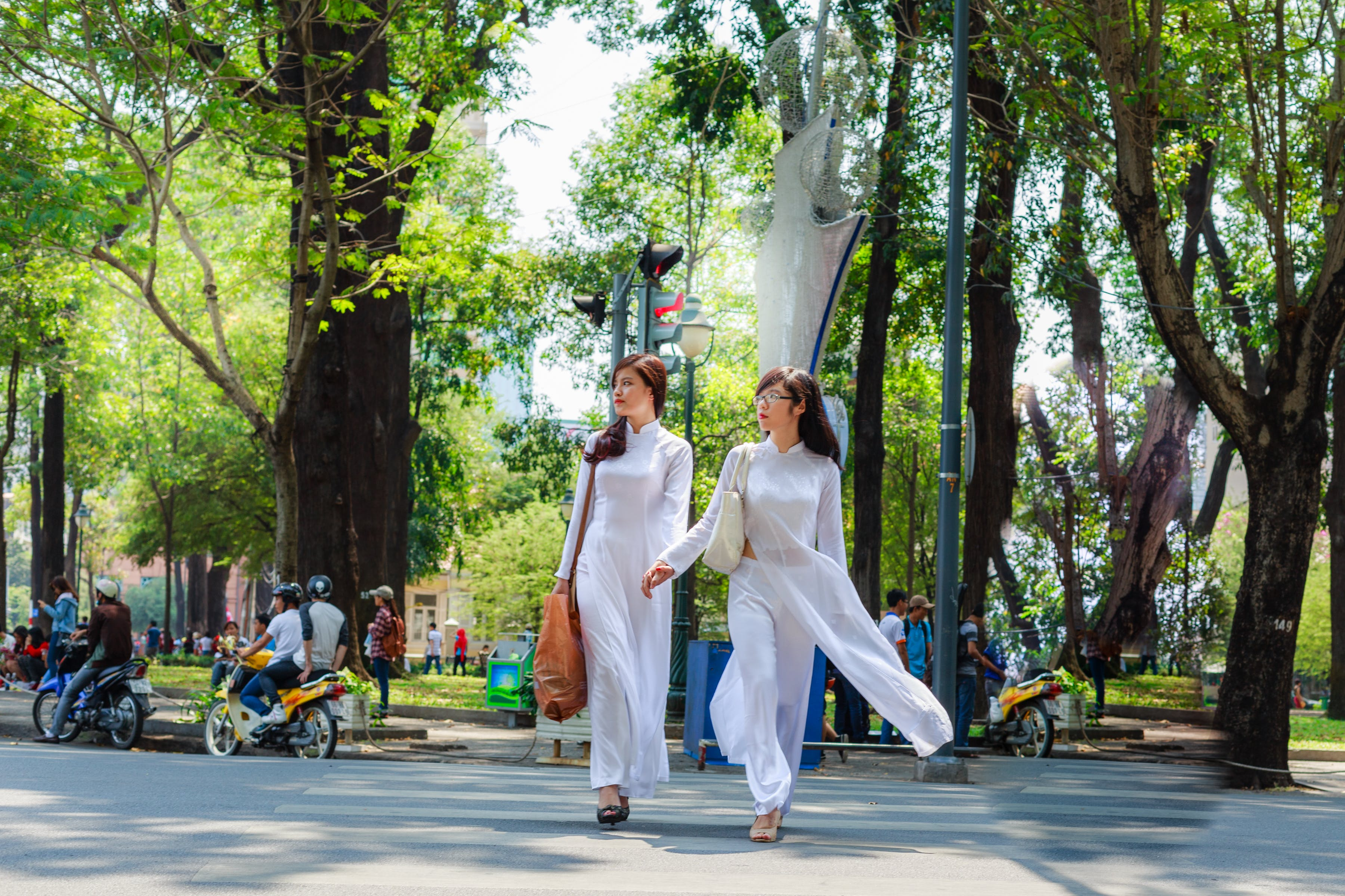 Photo of Two Women In White Outfits Holding Hands While Crossing the Street