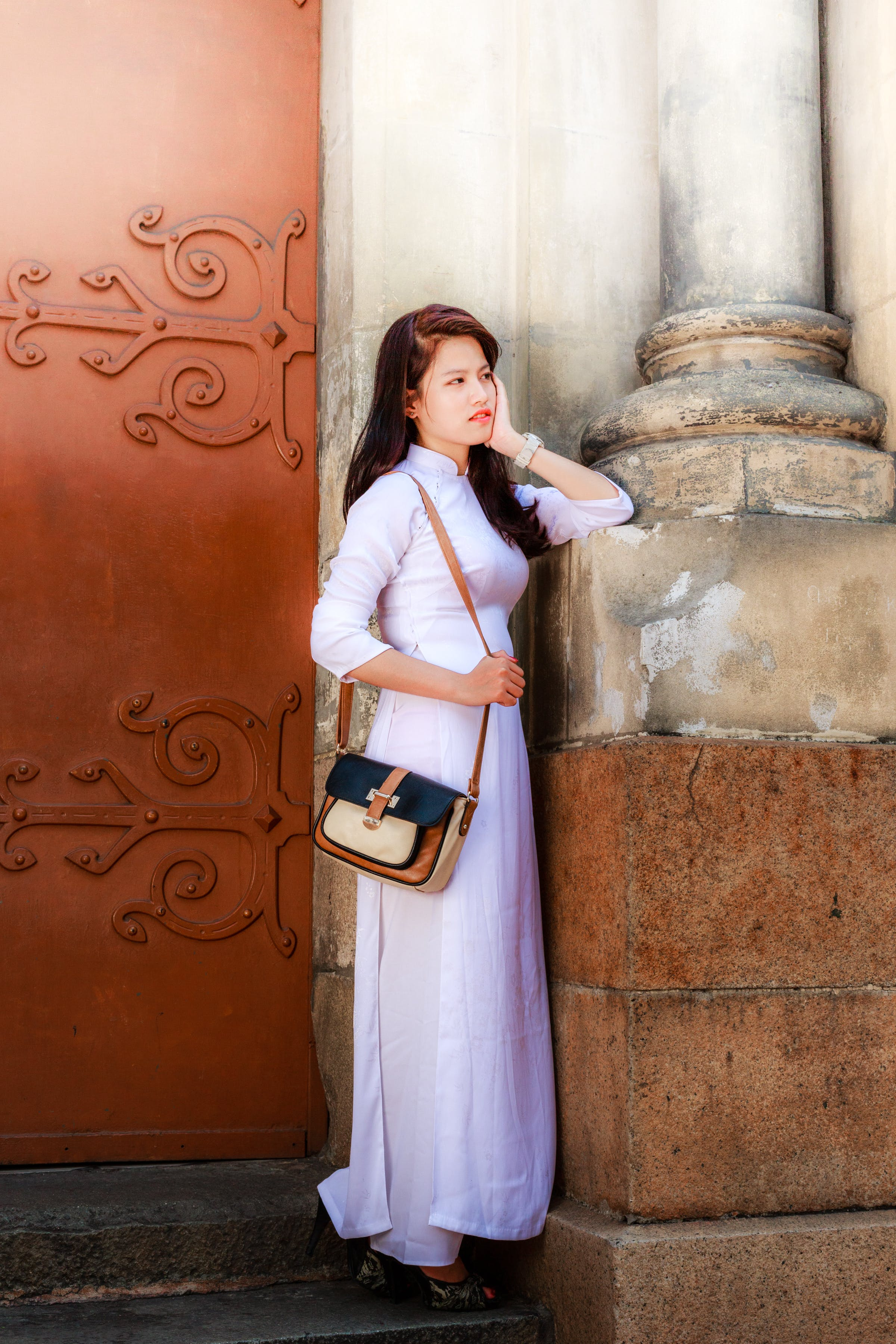 Photo of Woman in White Outfit Standing In front Of Brown Door Holding Her Cheek