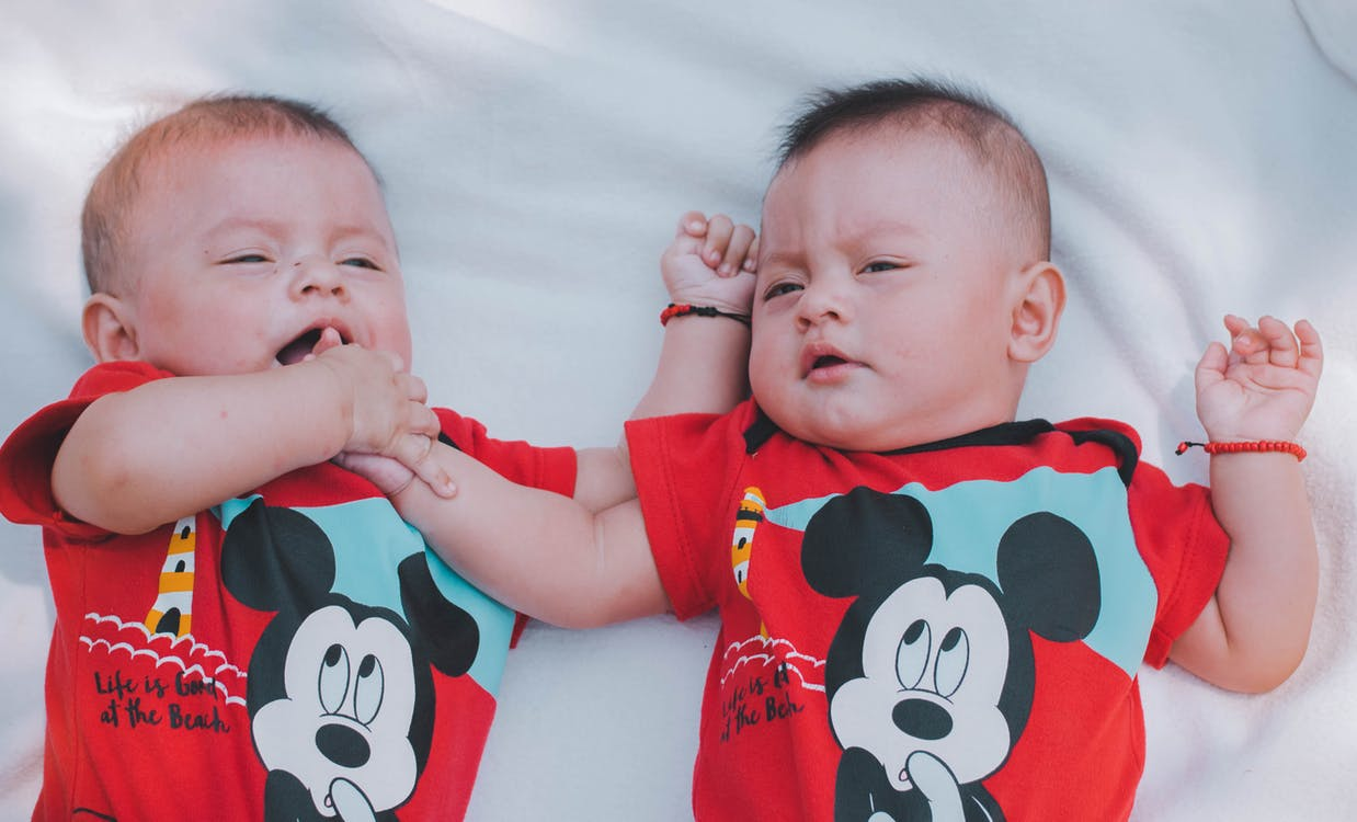 Two Babies Wearing Red Mickey Mouse Shirts