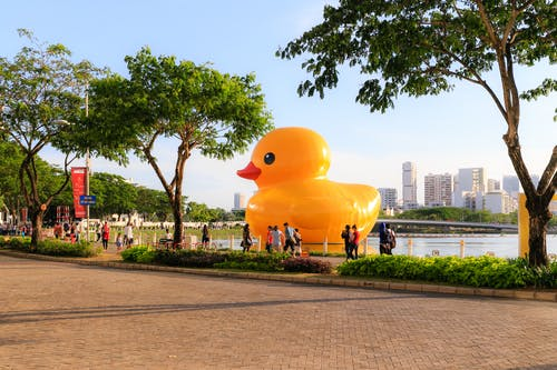 Giant Rubber Ducky on Body of Water at Park With People