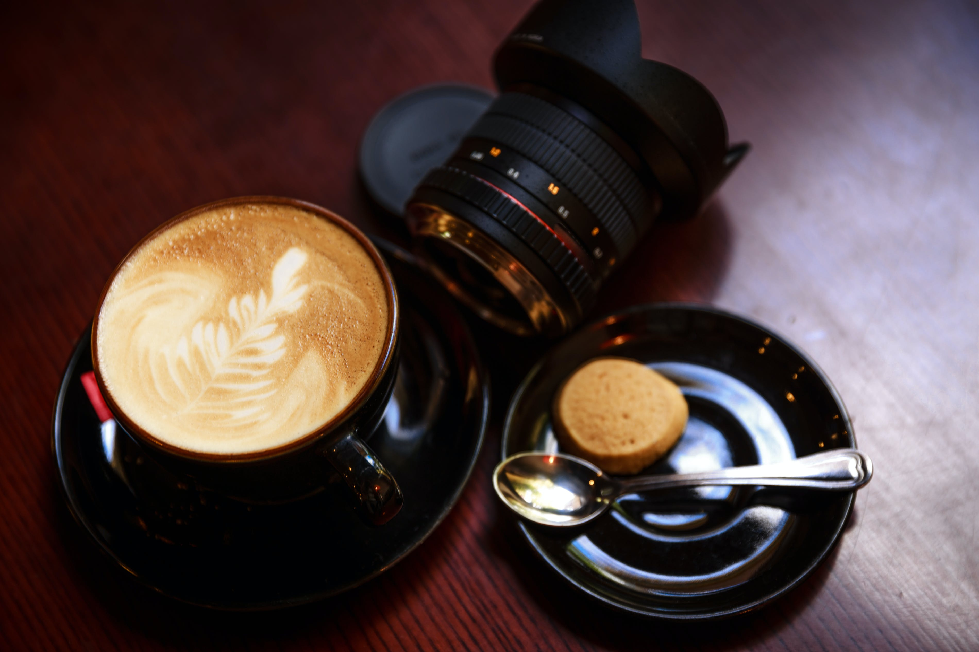 Black Teacup Filled With Coffee Beside Camera Lens