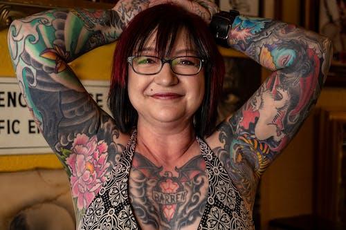 Женщина с татуировкой на покрытом теле в бюстгальтере