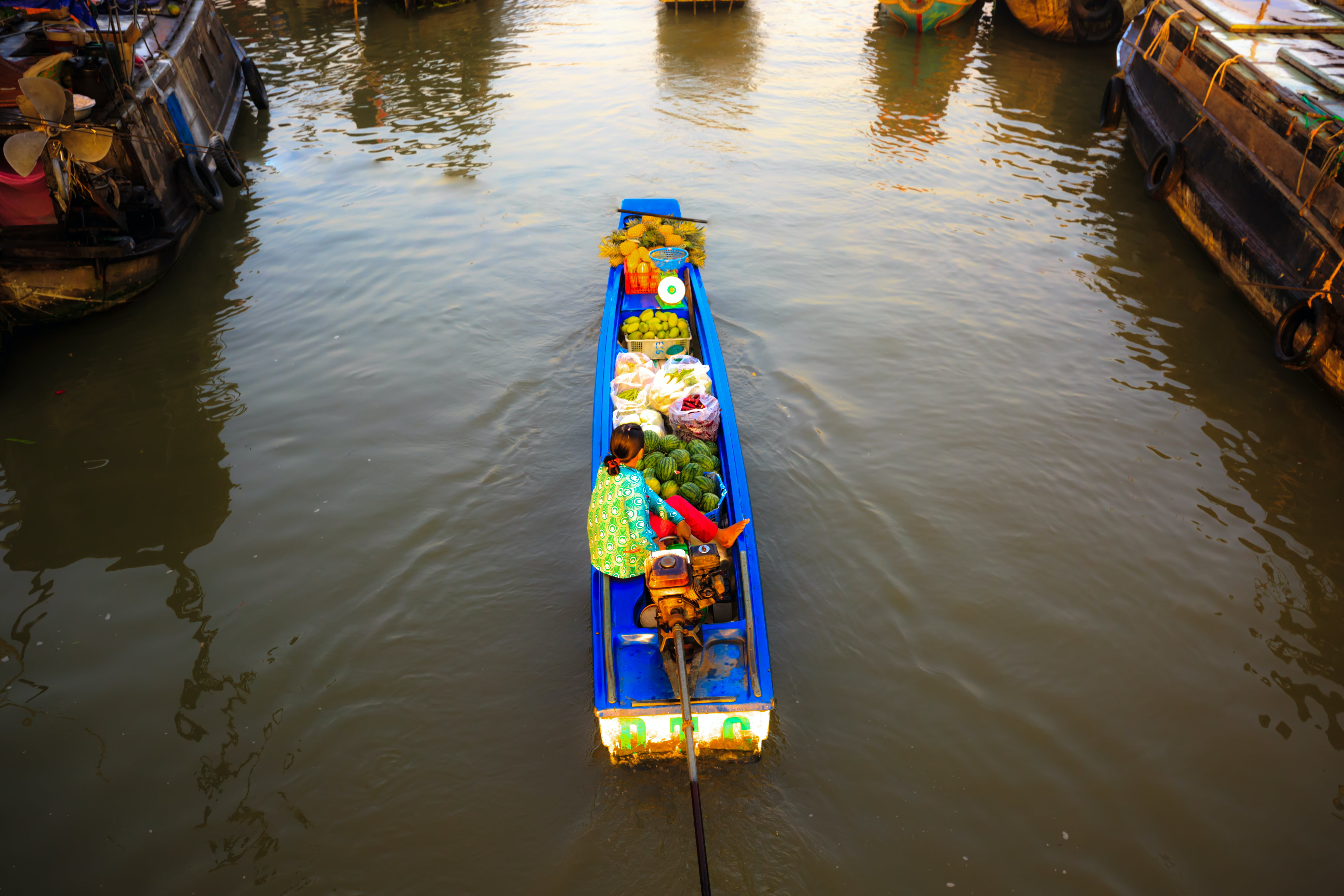 Woman in River Boat Full of Fruits and Vegetables