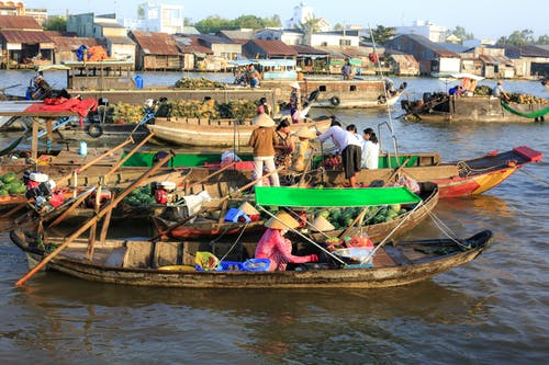People Sitting and Standing on Boats With Different Goods on Display Near Houses