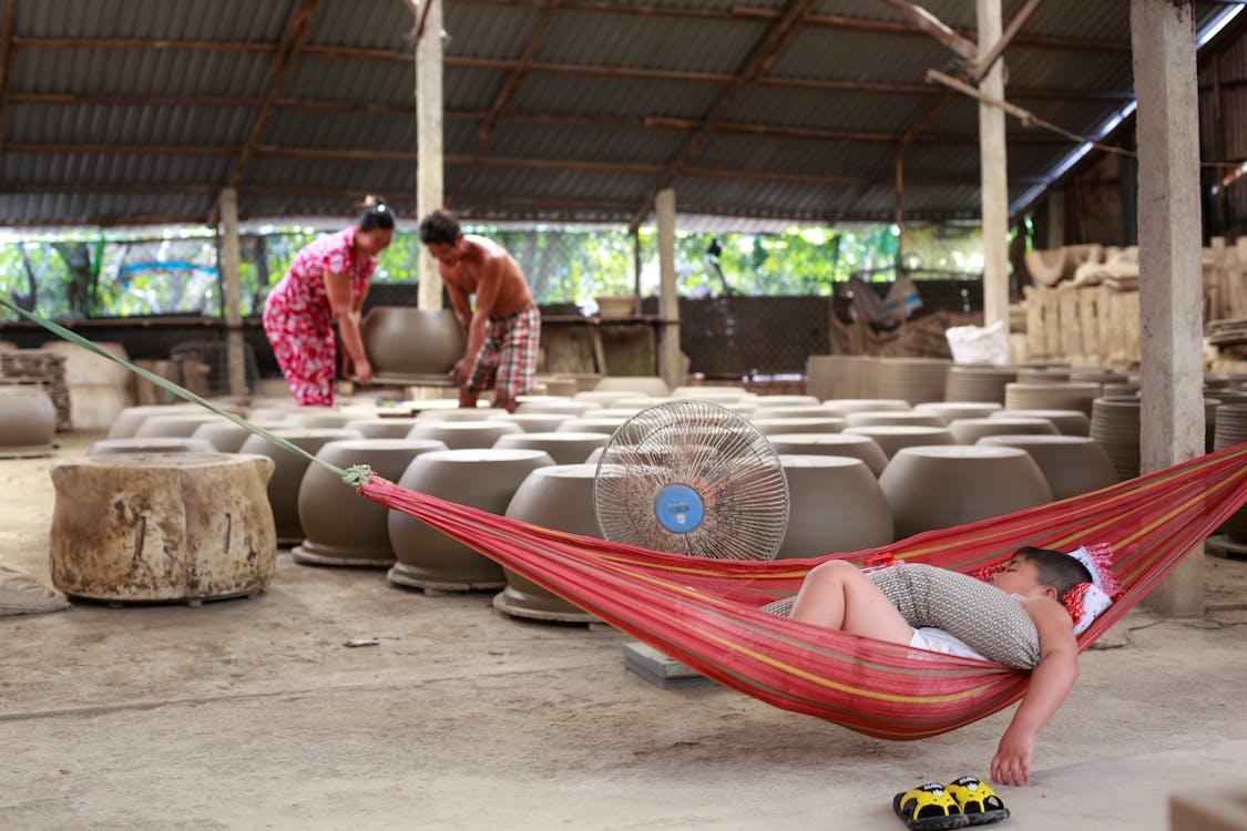 Man Sleeping on Red Hammock Near Clay Pots
