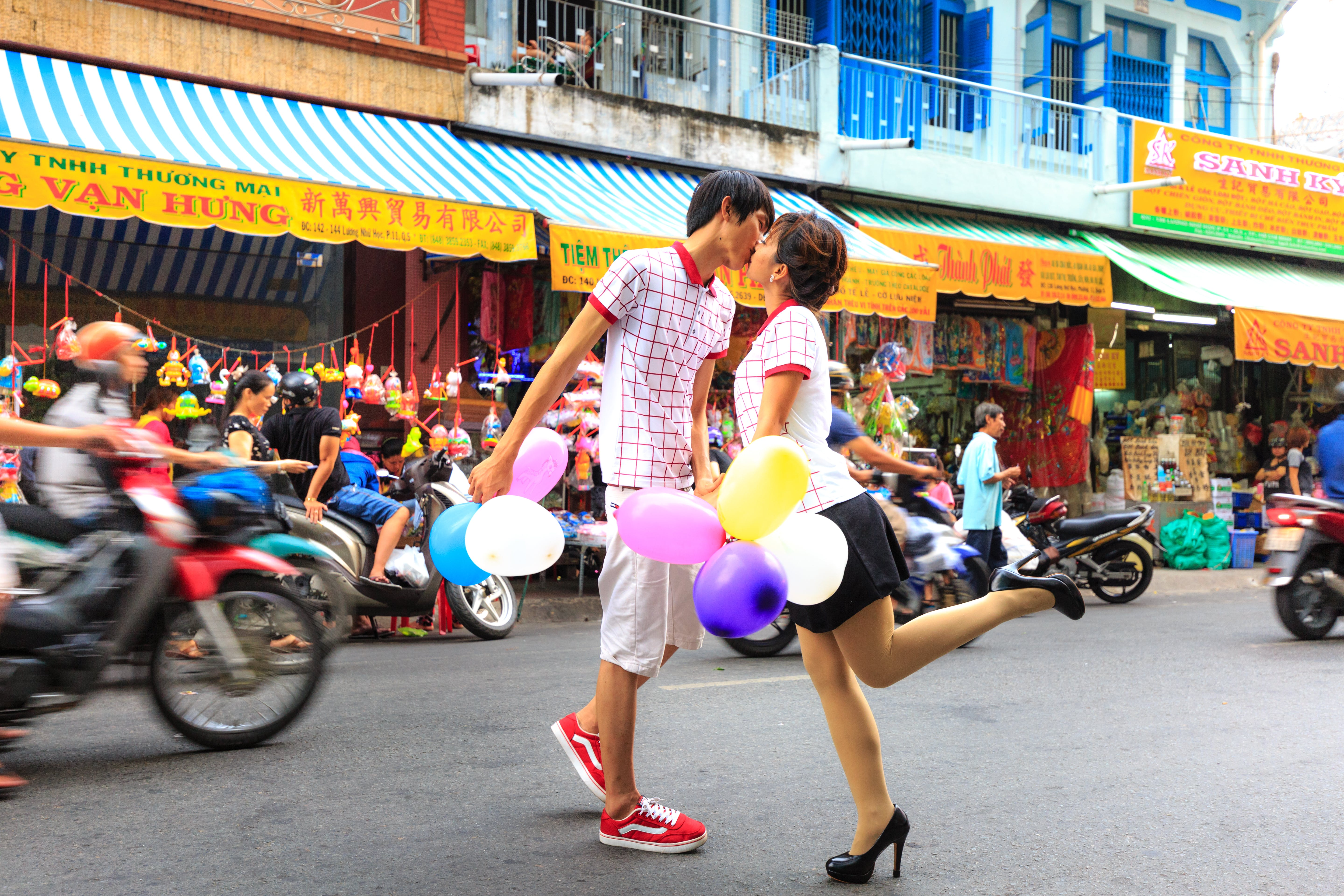 Man Kissing Woman While Holding Balloons