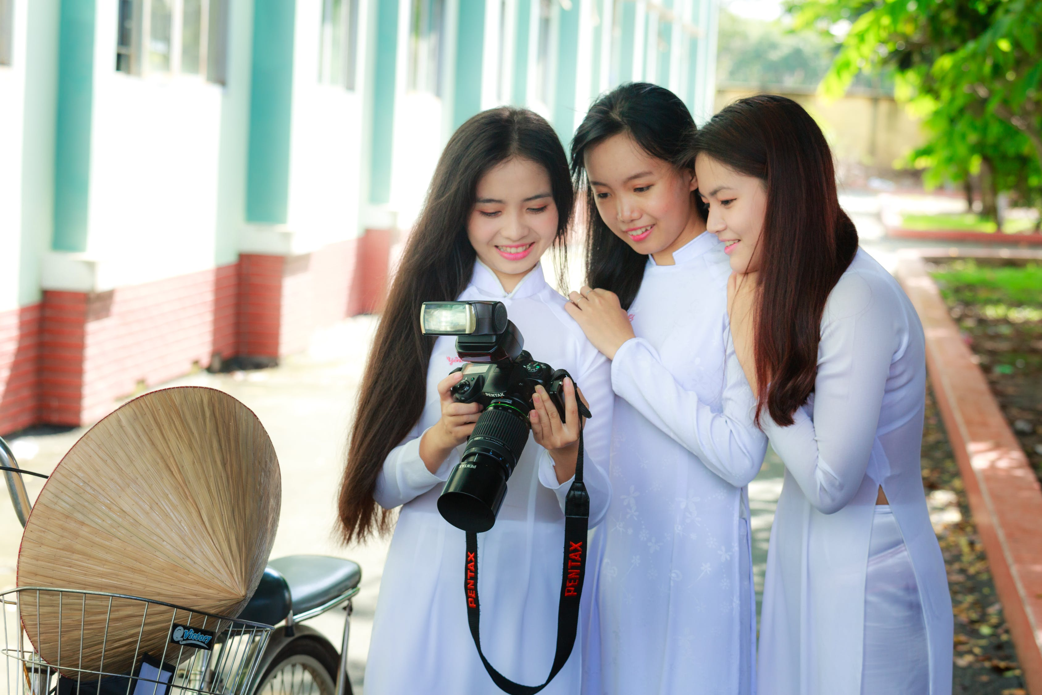 Photo of Three Women in White Outfits Checking Photos on The Screen of a DSLR camera.