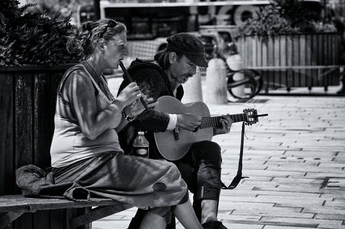 Greyscale Photography of Man and Woman Playing Musical Instruments