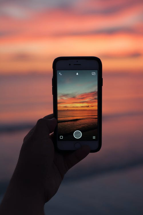Person Holding Iphone Taking Picture on Ocean With Sunset Background