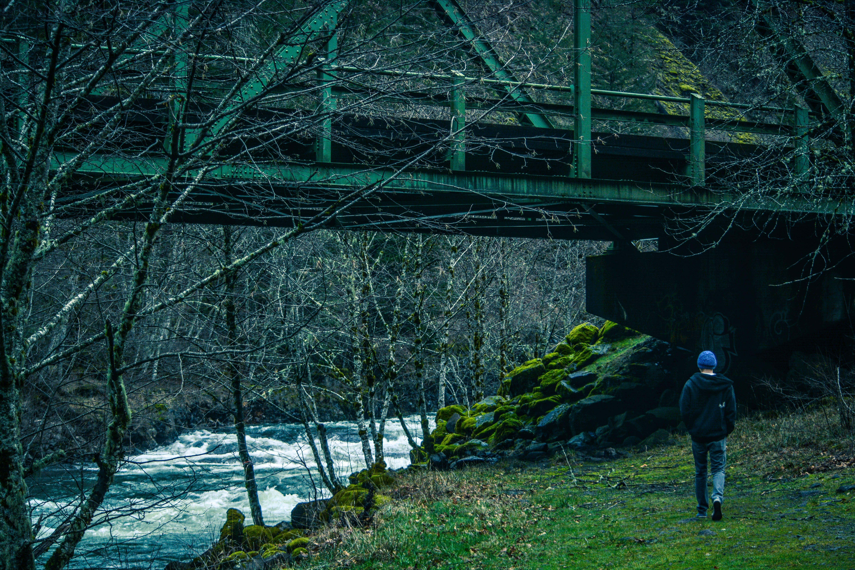 Man Walking Under Bridge Beside River