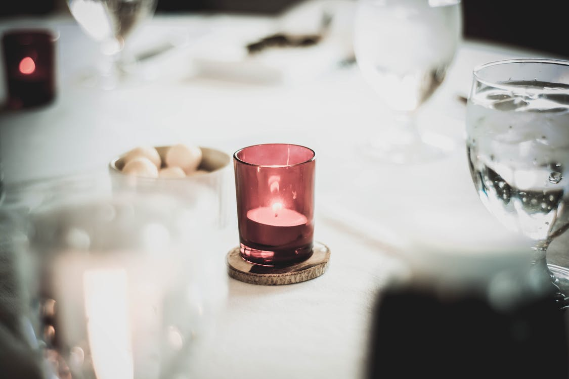 White and Red Votive Candle on Table