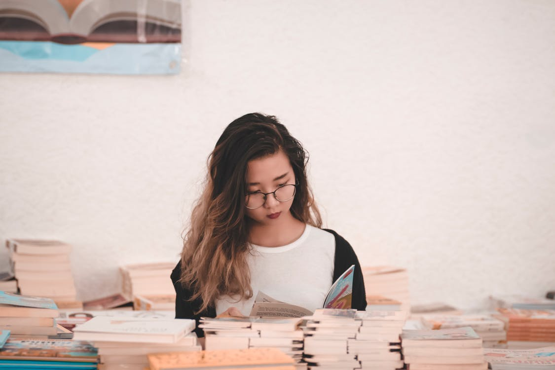 Photo of Woman Reading Book in Room Full of Books