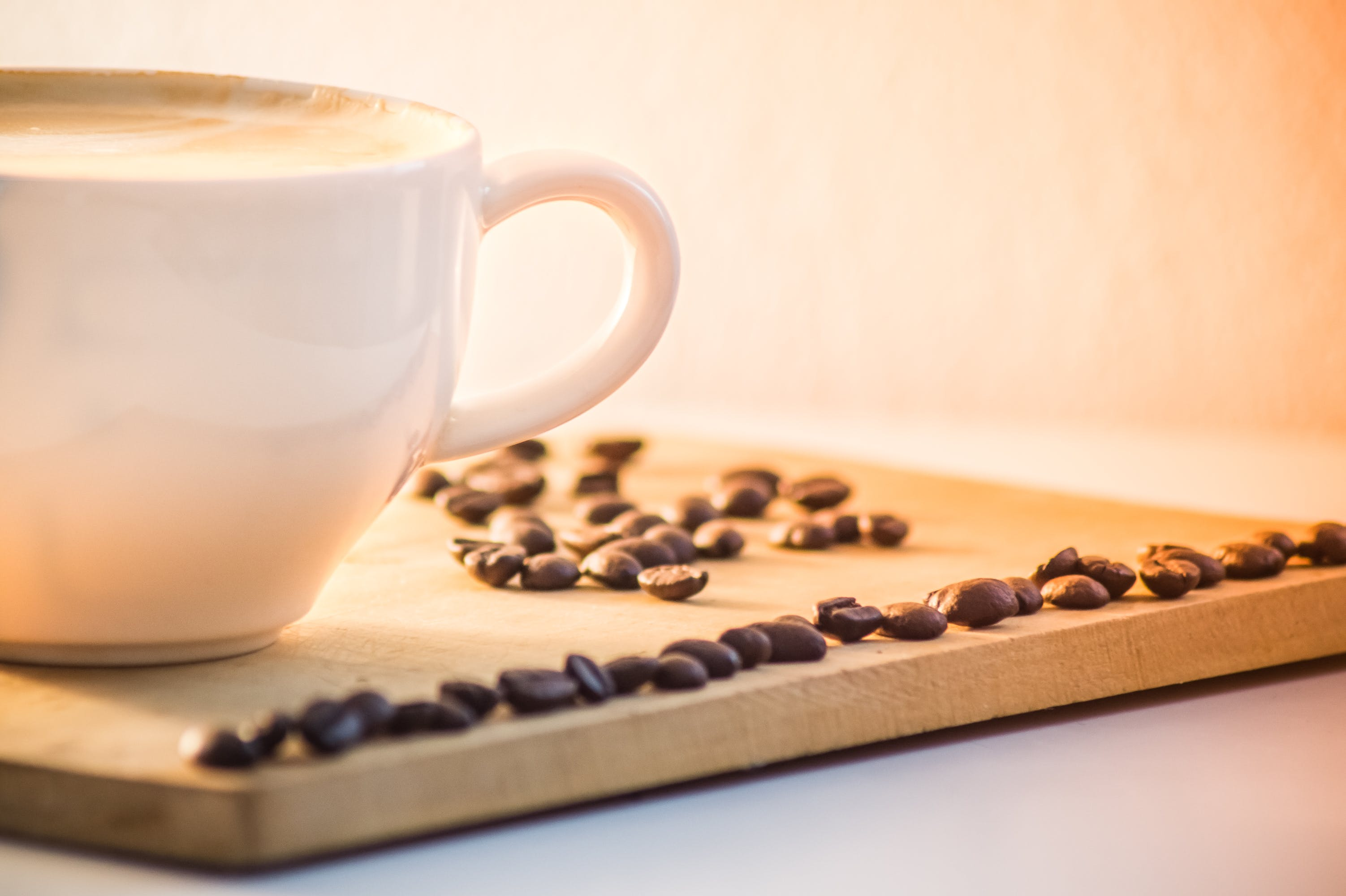 White Ceramic Coffee Mug With Cream Beside Black Coffee Beans
