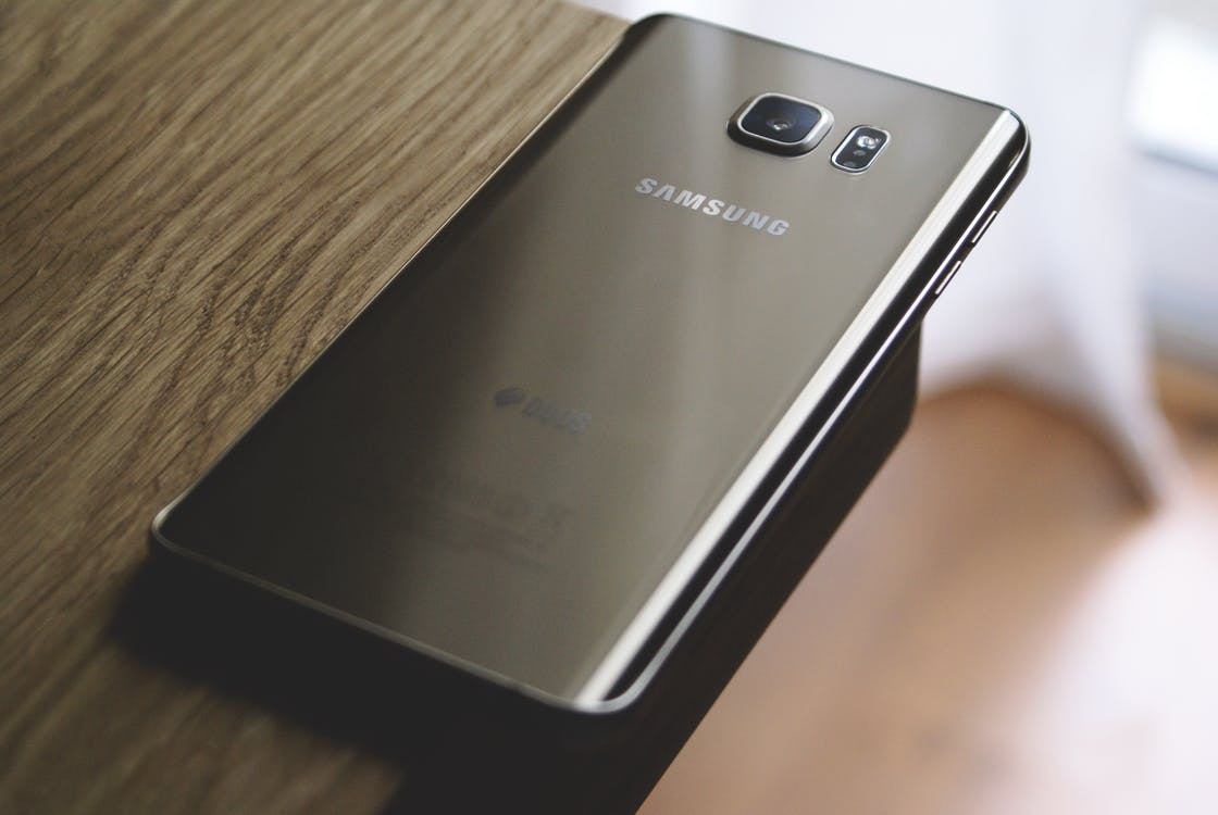 Silver Samsung Galaxy Smartphone on Top of Brown Wooden Table
