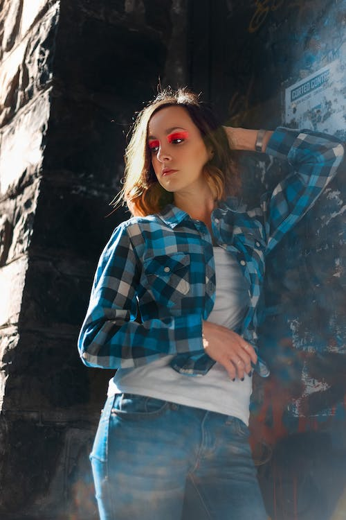 Photo of Woman in Blue and White Plaid Shirt and Blue Denim Jeans Posing
