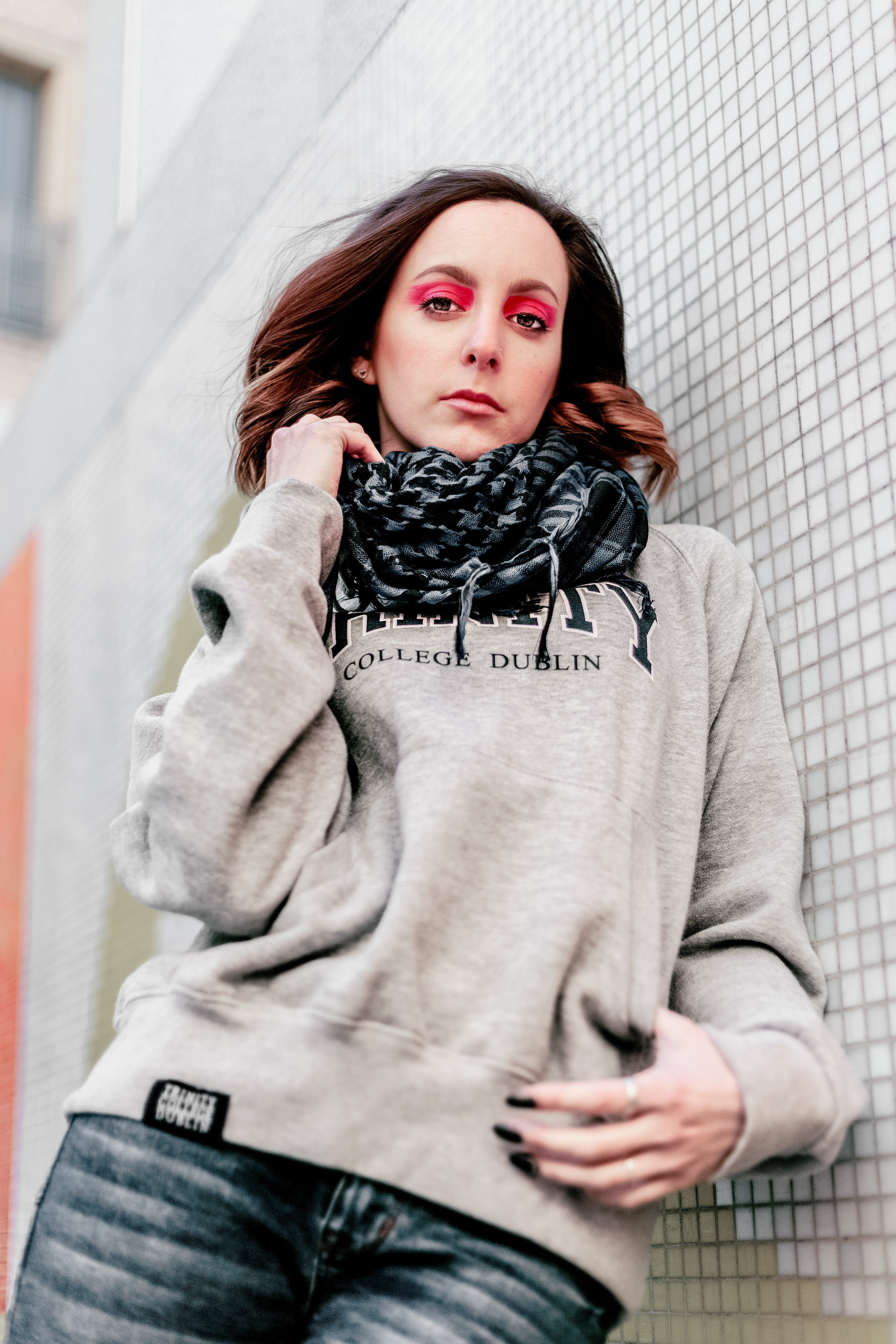 Woman in Gray Hoodie Leaning on Wall