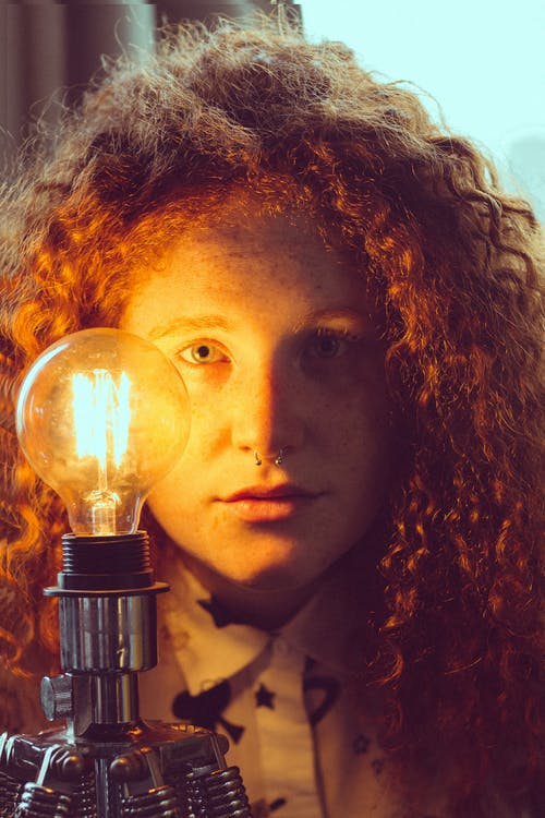Woman Standing Near Light Bulb