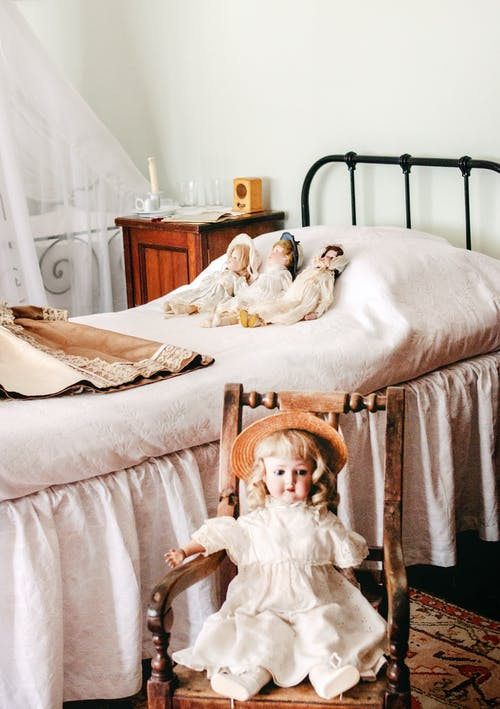 Three Dolls Lying on Bed