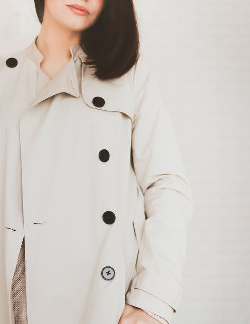 Woman Wearing Beige Coat in Front White Wall