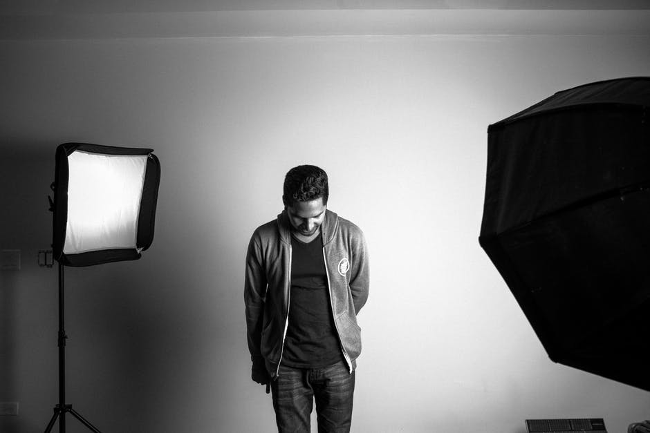 Grayscale photography of standing man in studio