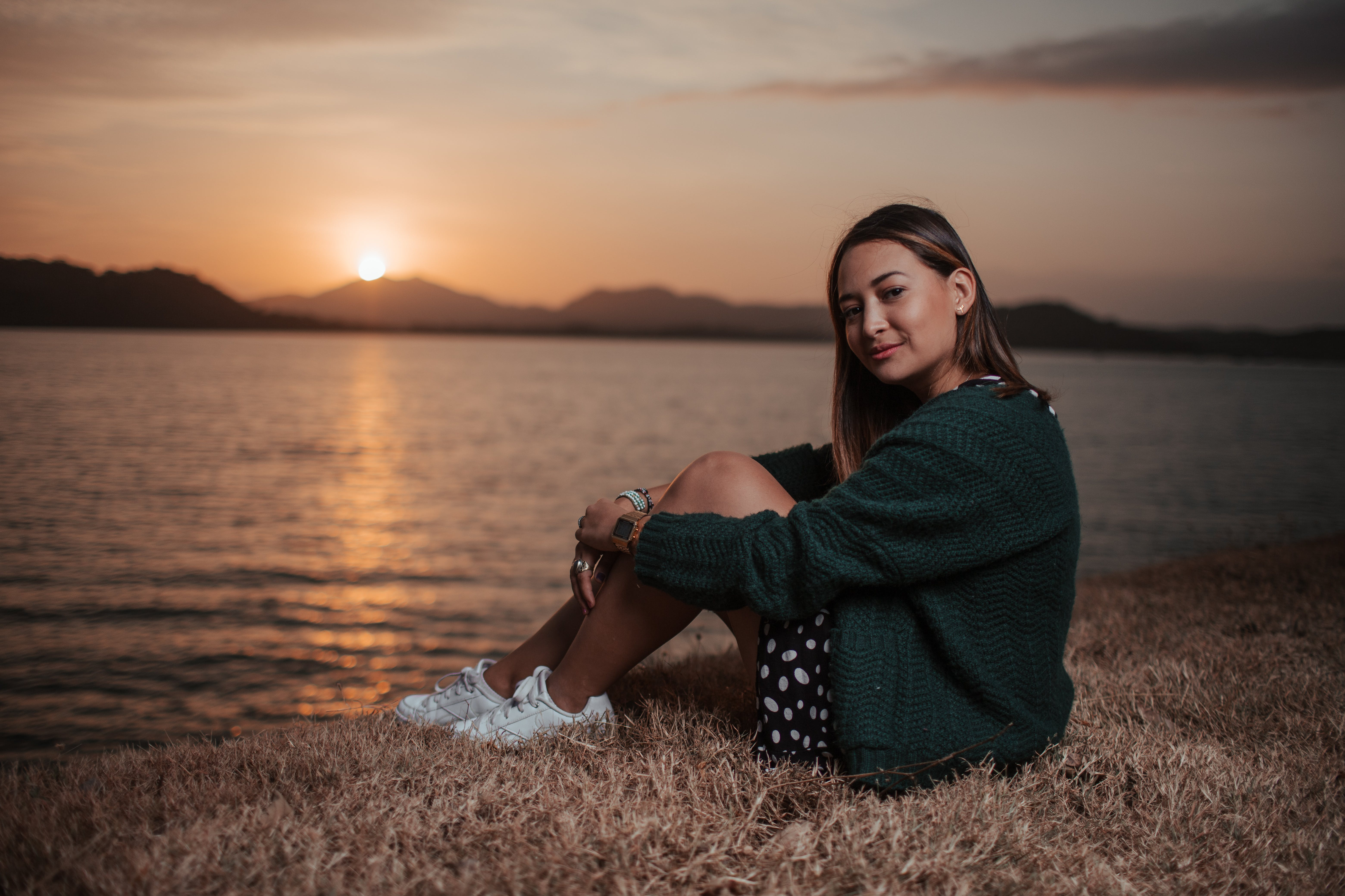 Woman Sitting Near Calm Body of Water during Sunset