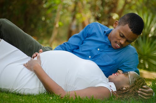 Pregnant Woman Lying Beside Man in Grass Ground