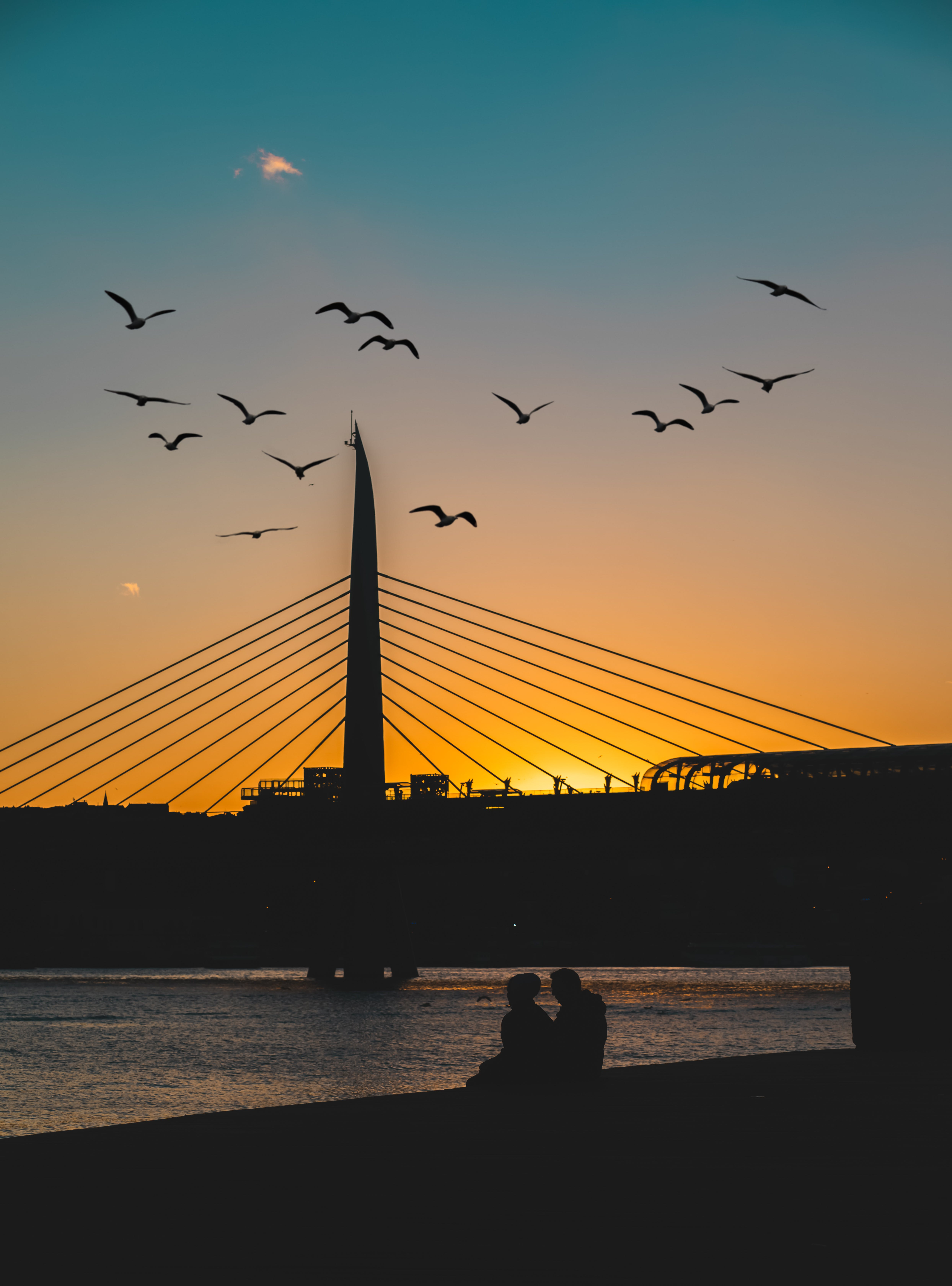 Silhouette of Bridge With Two People on Side of Body of Water