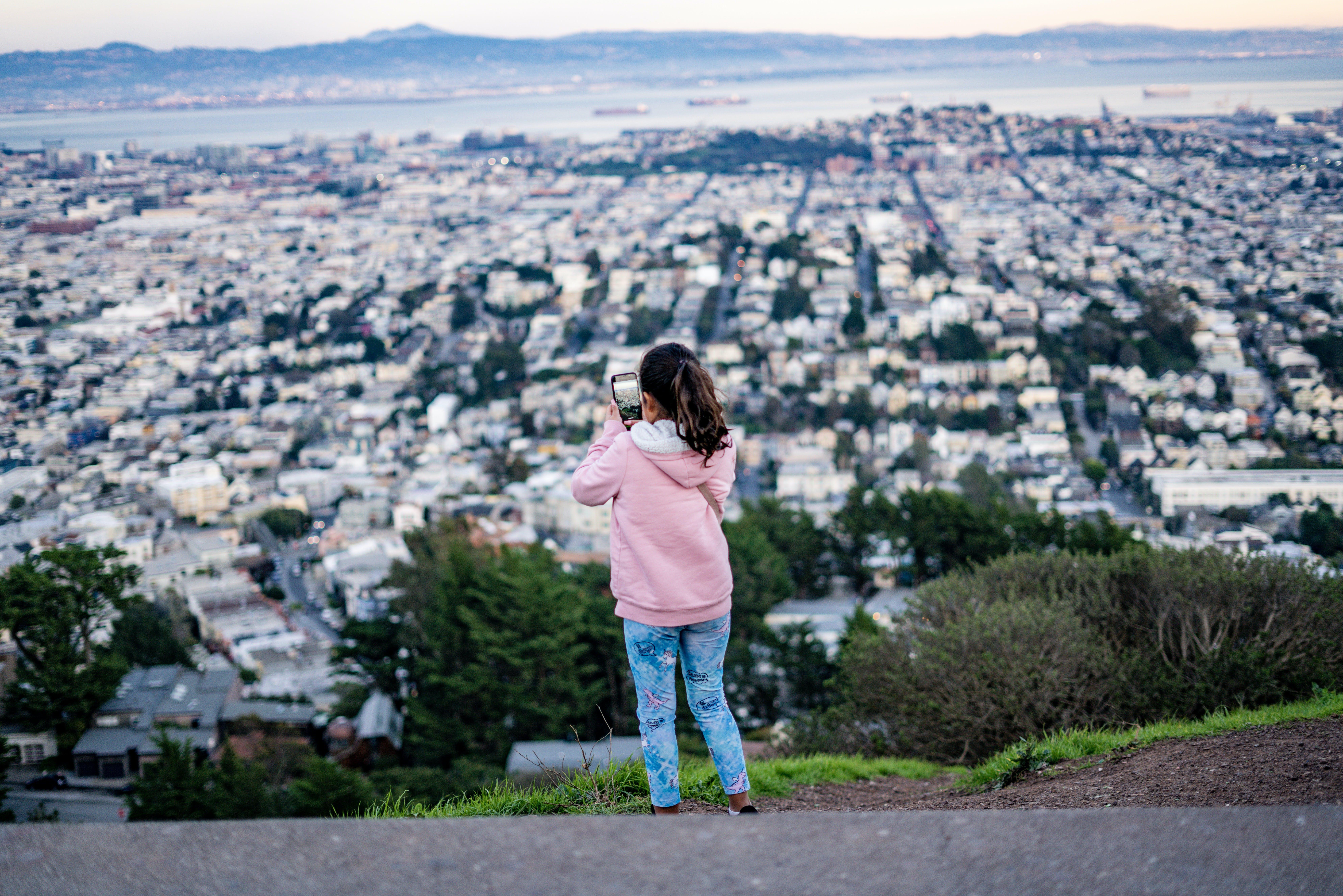 Girl Wearing Pink Hoodie Taking Photo of City