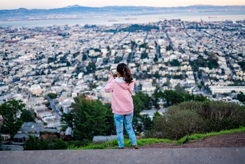 Girl Wearing Pink Hoodie Taking Photo of City