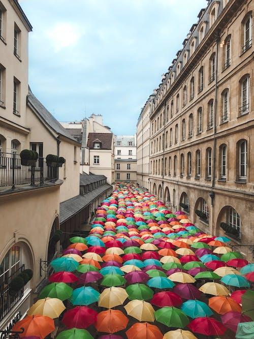 Assorted-color Umbrellas Between Buildings