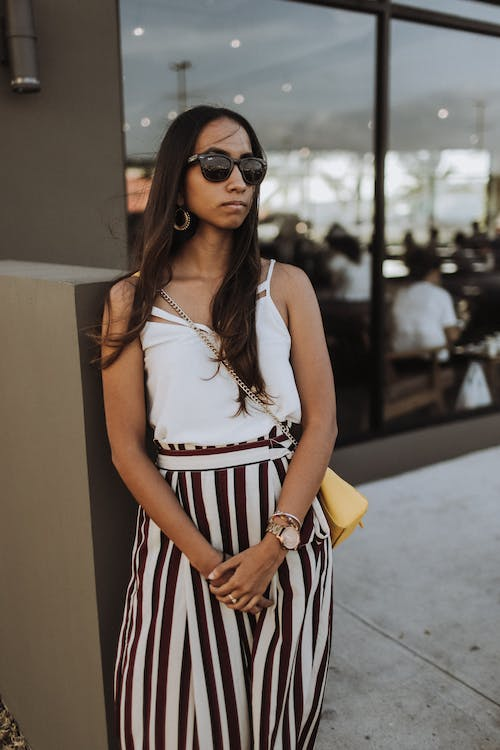 Woman Wearing White Spaghetti Strap Top And Sunglasses Standing Against Wall